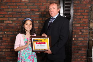 AAA Director of Traffic John Corlett presents a second place award to Stewart School fifth-grader Dian Wakeham (Photo by Marquee Photography)