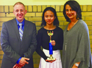 Lela Immanuel is pictured here with her trophy and Señora Caruthers and world languages coordinator Peter Giacalone.