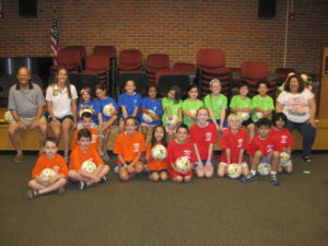 The Garden City Centennial Soccer Club participated in the second-grade book discussion of  Soccer Sam. Chair of the library board of trustees and former Centennial President J. Randolph Colahan (left) and Jenn Costa  (second left) are pictured with soccer players and book discussion participants and Children's Librarian Donna Furey (right).