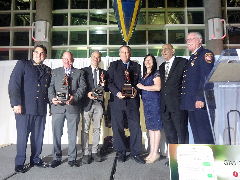 From left: Badge of Courage honorees John Feal (second from left), Jon Stewart (third from left) and Ray Pfeifer (fourth from left) along with Firefighters Museum Executive Director Alana Petrocelli (third from right) (Photo by Chris Boyle)